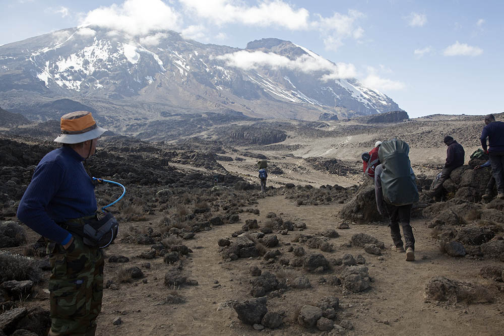 Stepping aside while our high speed porters get moving Mt Kilimajaro